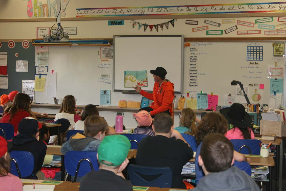 OSU student athlete reading a Dr. Seuss book to elementary students.