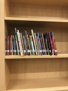 Books are going on the shelves in our new library!